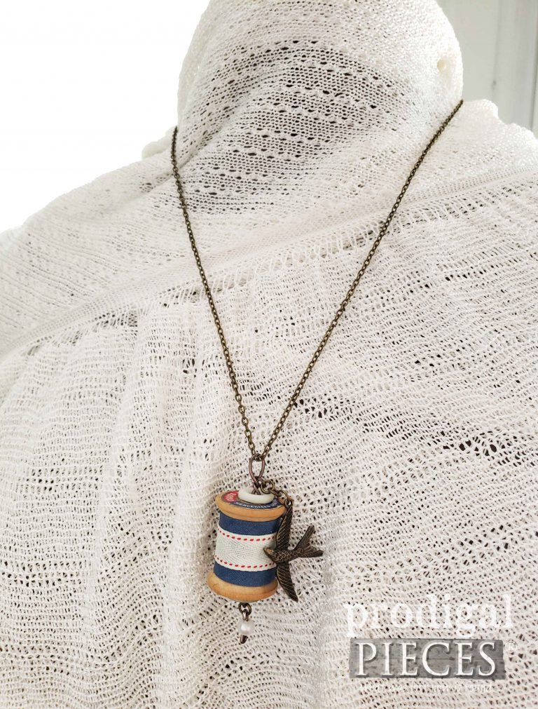Brass Bird Charm with Blue Accent Ribbon on Wooden Spool Necklace | shop.prodigalpieces.com